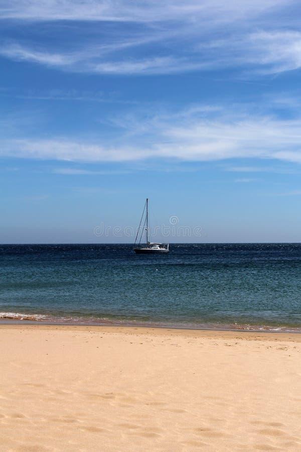 Empty beach and yacht at sea. Empty sandy beach and yacht at sea stock photos