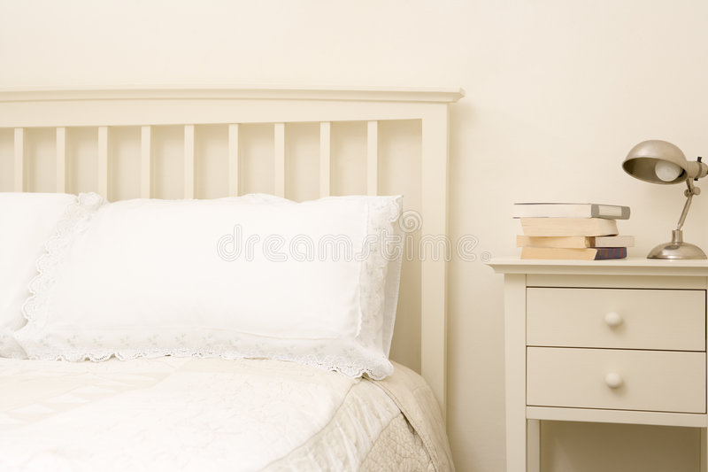 Empty bedroom with books on nightstand royalty free stock images