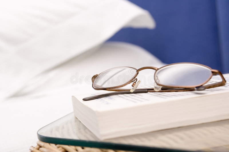 Empty bedroom with focus on eyeglasses and book royalty free stock image