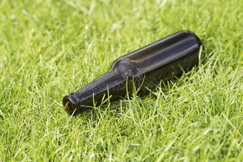 Empty beer bottle in the grass. Empty beer bottle in a grass field with a vague background stock photos