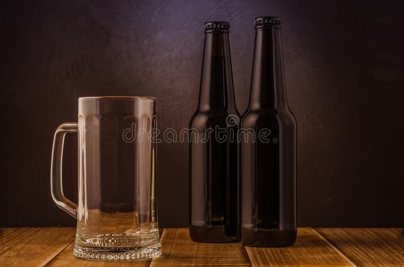 Empty beer glass and two bottles/ empty beer glass and two bottles on a bar. Empty beer glass and two bottles/empty beer glass and two bottles on a bar royalty free stock photo