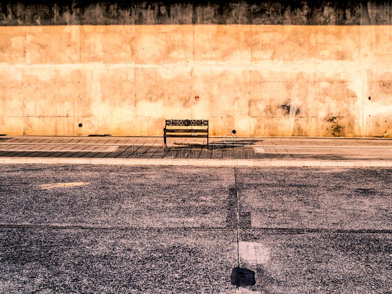 An empty bench against a old rustic concrete next to the street in Bangkok Thailand summer time royalty free stock photo