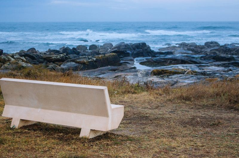 Empty bench on Atlantic Ocean coast in Portugal in the morning. Seascape in blue morning fog. Ocean beach with rocks. stock photo