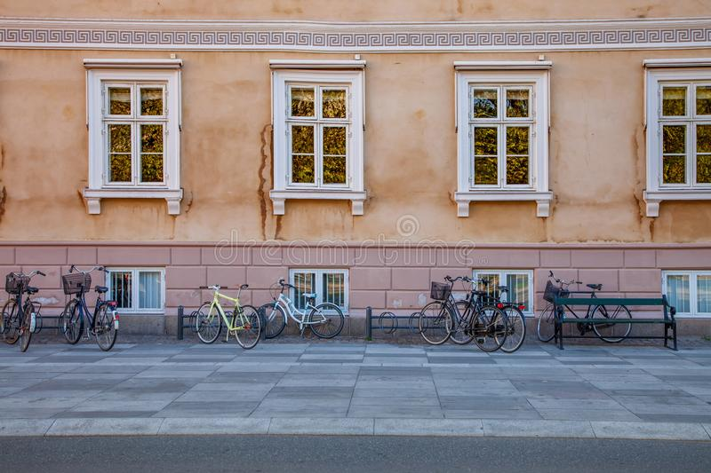 Empty bench and bicycles parked near old house on street. In copenhagen, denmark stock images