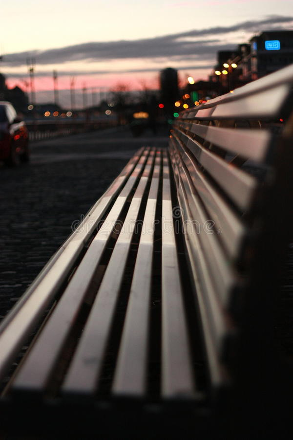 The empty bench. The night begins to cover dublin, ireland and the light of the sunset and the city reflect on a lonesome left bench expecting the tourists of royalty free stock images