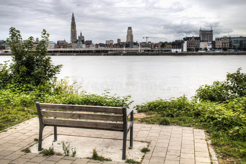 Empty bench overlooking the Antwerp skyline with the schelde river royalty free stock images