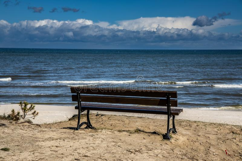 Empty bench standing on the dunes on the Polish coast on the Baltic Sea beach on a beautiful sunny day royalty free stock images