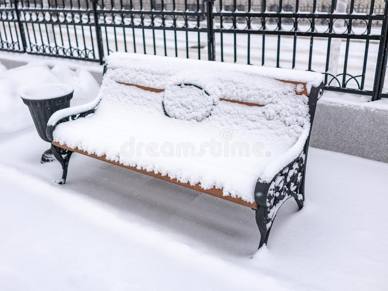 Empty bench in the winter park covered with fresh white snow royalty free stock images