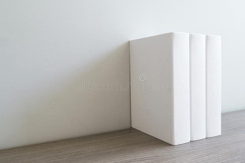Book with empty blank cover on white bookshelf. stock photos