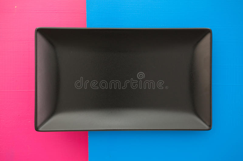 Empty black ceramic dish on over blue and pink background, rectangle dish. Empty black ceramic dish on over blue and pink wooden table, rectangle dish royalty free stock photography