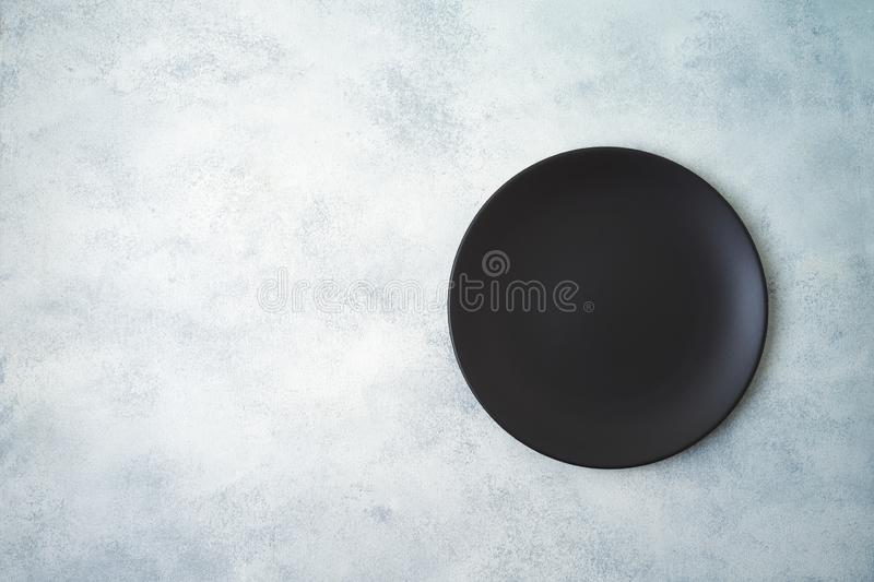 Empty black plate on gray stone table background. Empty black  plate on gray stone table background. Top view from above royalty free stock photo