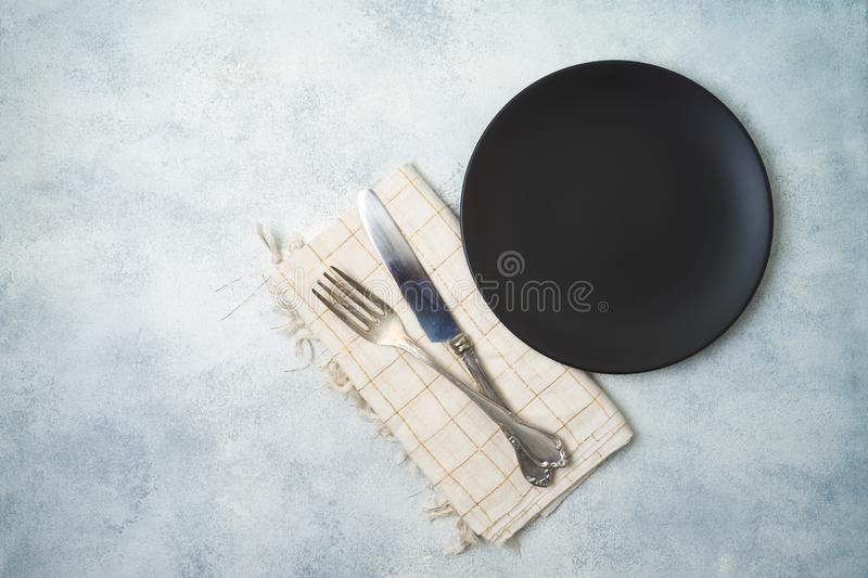 Empty black plate on gray stone table background. Top view from above stock images