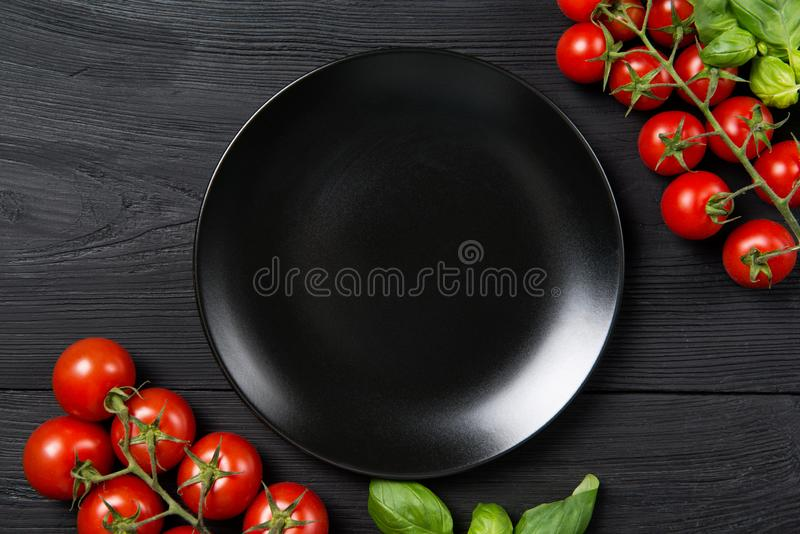 Empty black plate on a black wooden table with red ripe cherry tomatoes and basil leaves, top view with copy space stock photography