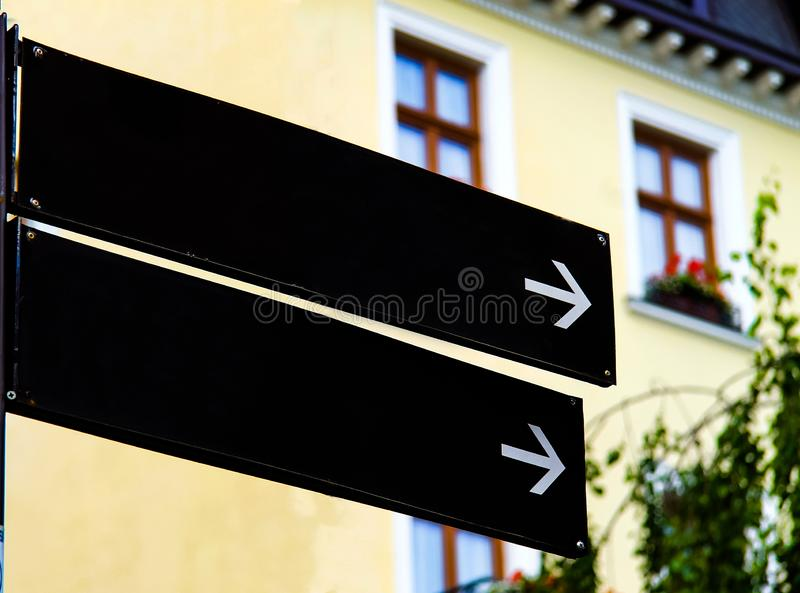 Empty black road signs or blank road signs showing direction against a building. stock photo