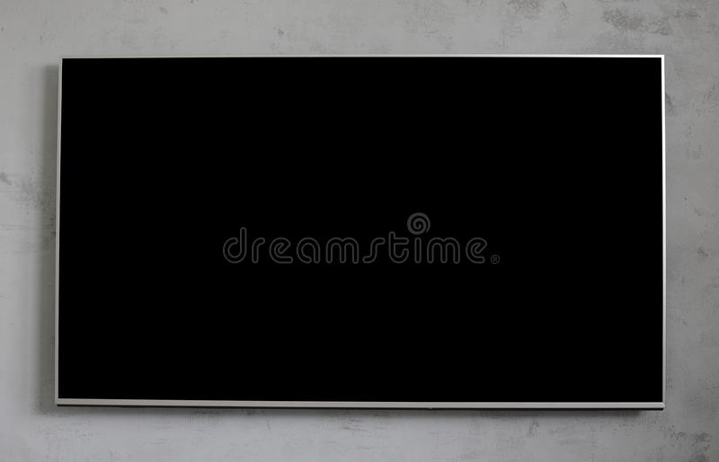 Empty black television screen on concrete wall. royalty free stock photography