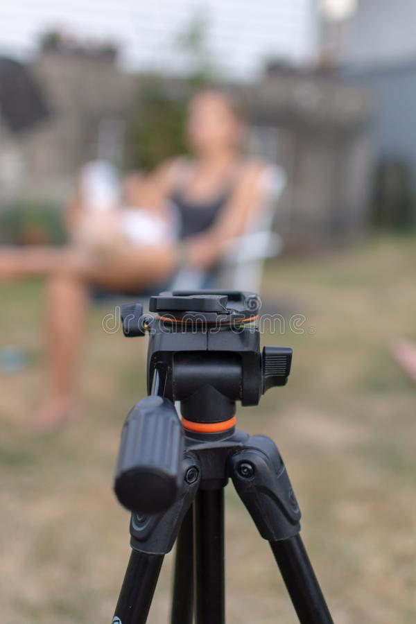 An empty black tripod looking towards a blurred women and child outdoors for a photography shoot. Conceptual stock photos