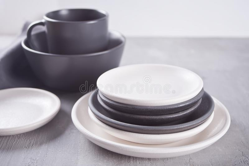 Empty black and white plates over gray table. Asian kitchen oriental traditional minimalism pottery empty food and soup black and white ceramic plates on the royalty free stock image