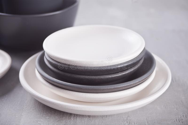 Empty black and white plates over gray table. Asian kitchen oriental traditional minimalism pottery empty food and soup black and white ceramic plates on the royalty free stock photography
