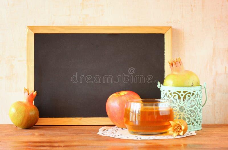 Empty blackboard, apple, honey and pomegranate. rosh hshanah concept. stock photos