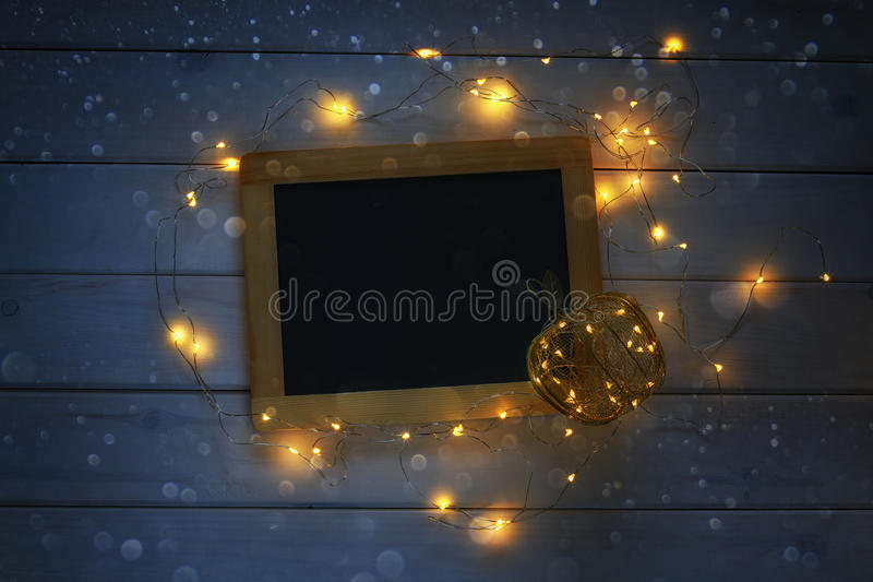 empty blackboard and decorative gold apple with lights royalty free stock image
