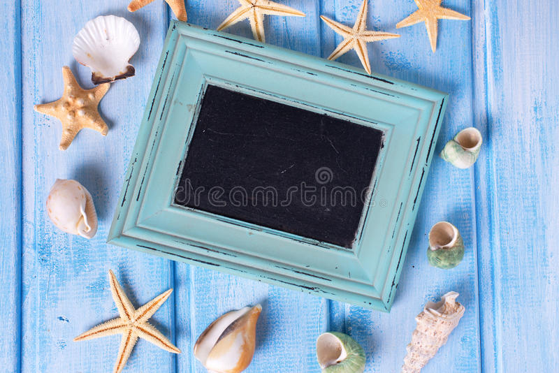 Empty blackboard and different marine items on blue painted w stock image
