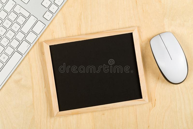 Empty, blank, black chalkboard with computer mouse and keyboard on brown wooden table flat lay from above. With copy space - e-learning or computer science royalty free stock photo