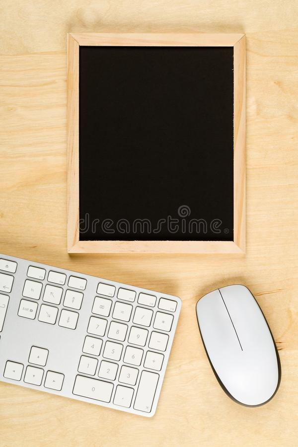 Empty, blank, black chalkboard with computer mouse and keyboard on brown wooden table flat lay from above. With copy space - e-learning or computer science royalty free stock photography