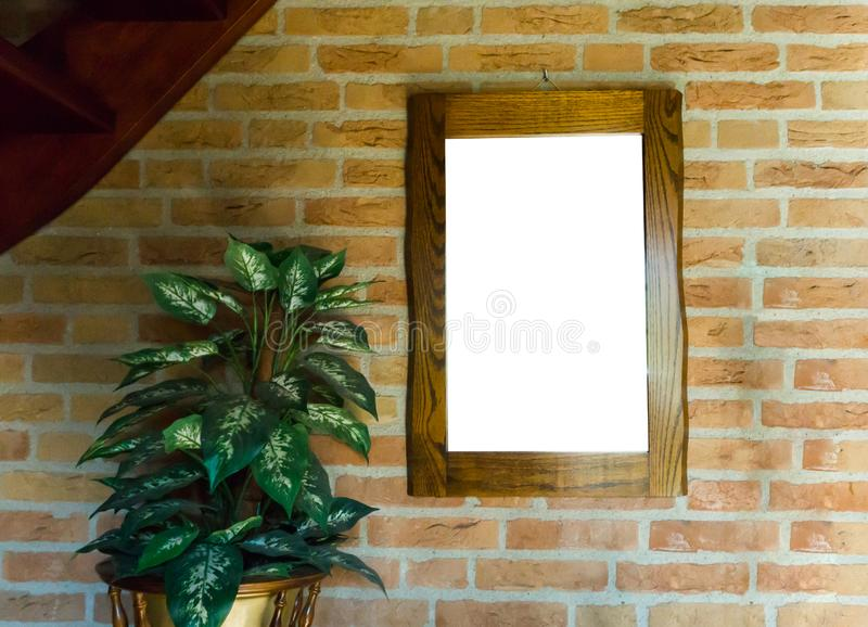 Empty blank cut out wooden mirror or painting frame hanging on a brick wall in a room decorated with a house plant. A empty blank cut out wooden mirror or royalty free stock photography