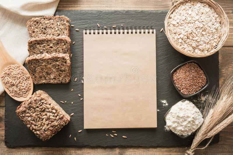 Empty blank for a recipe of bread with ingredients, flour, wheat, bread, rye, flax seeds around on black slate dish.Top view and c stock image