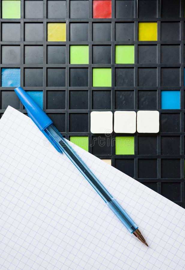 Empty blank scrabble pieces on game board, pen and white paper royalty free stock images