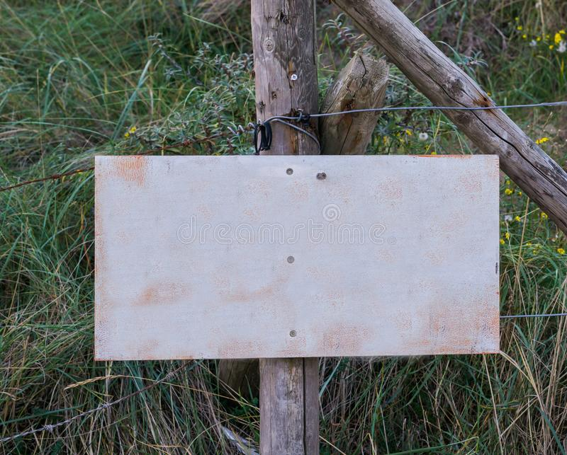 Empty blank signboard plate on a pole to put whatever you want in a nature landscape with grass. A empty blank signboard plate on a pole to put whatever you want royalty free stock image