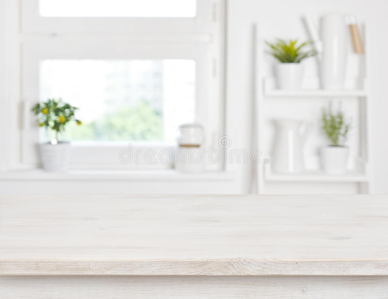 Empty bleached wooden table and kitchen window shelves blurred background stock photos