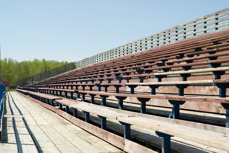 Empty Bleachers. Rows of empty wooden bleachers outside on a sunny day royalty free stock photography