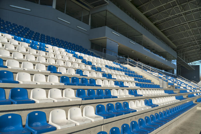 Empty bleachers - Stadium seats. Rows of empty bleachers positioned in a semicircular pattern. Stadium seats before an event stock image
