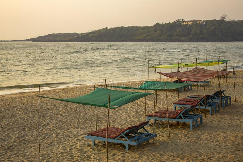 Empty blue beach beds under color awnings on the yellow sand against the background of the sea and the green island with the house. A empty blue beach beds under stock image