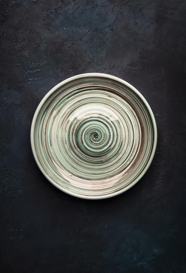 Empty blue ceramic plate on blue background, ready to serve, top view vertical royalty free stock image