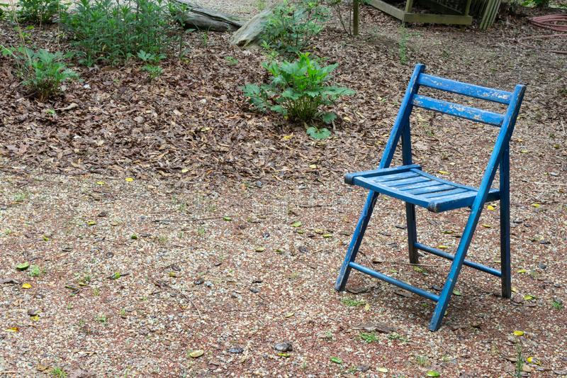 Empty blue folding chair outdoors, copy space, death grief absence concept. Horizontal aspect stock photography