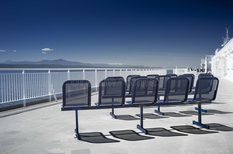 Empty blue metal ferry ship seats in sunshine. NANAIMO, BC, CANADA - MAY 27, 2017: Outdoor seats and Western view of clear blue sky and Strait of Georgia from royalty free stock images