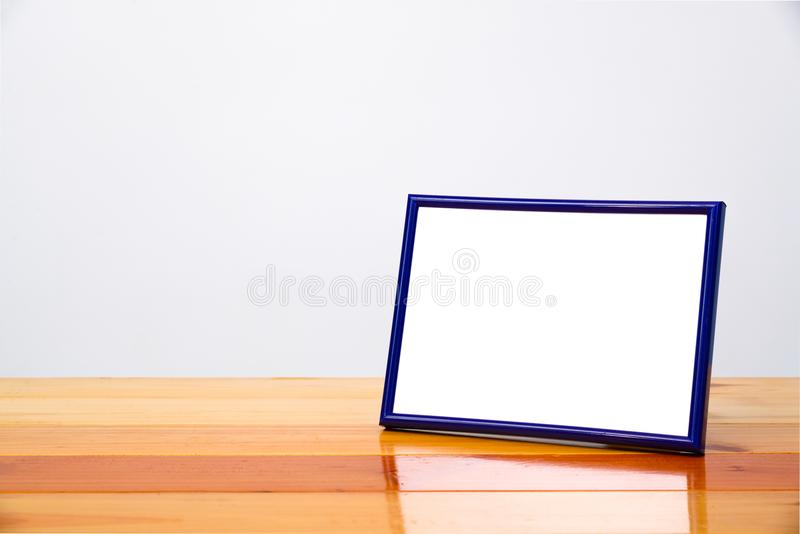 Empty blue photo frame on wooden table with copy space, picture royalty free stock photo