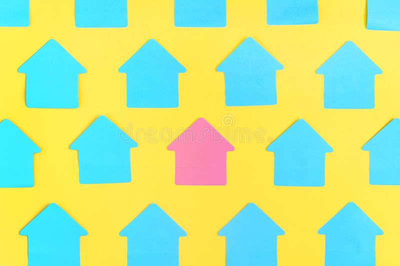 Empty blue stickers in the shape of a house, on a bright yellow background. In the center is a pink sticker. Empty stock image