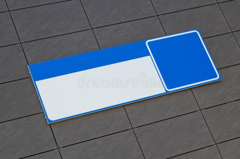 Empty blue and white rectangle metal plate, with no numerals. Sign of the adress of house or building. Plate placed on a royalty free stock photography