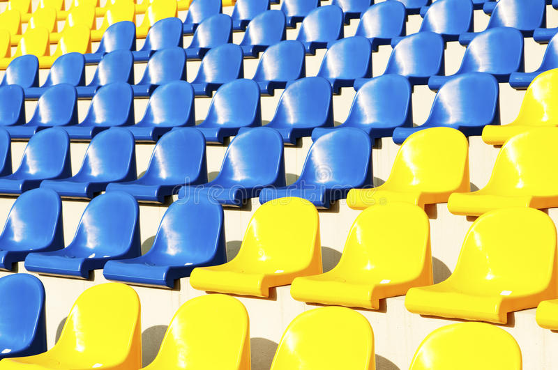 Empty blue and yellow seats in stadium. Photo of empty seats in the stadium stock images
