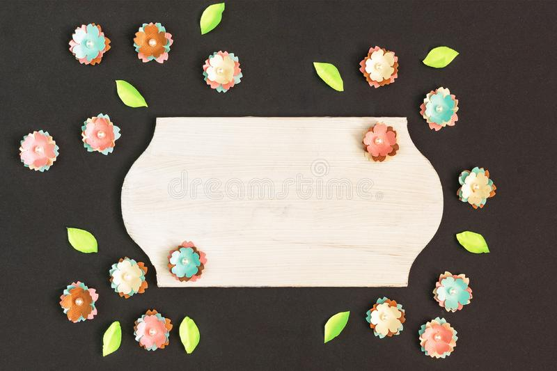 The empty board lies in the center of the black background. Around chaotically lie small artificial paper flowers royalty free stock image