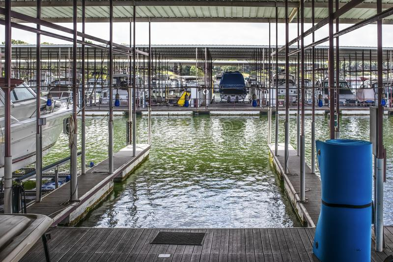 Empty boat slip in luxury boat dock at lake with other speedboats moored in distance - some up on racks and roller floater pad in stock photography