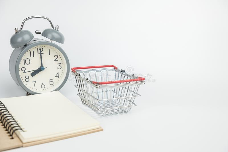Empty book and shopping cart with clock on white isolated background stock images