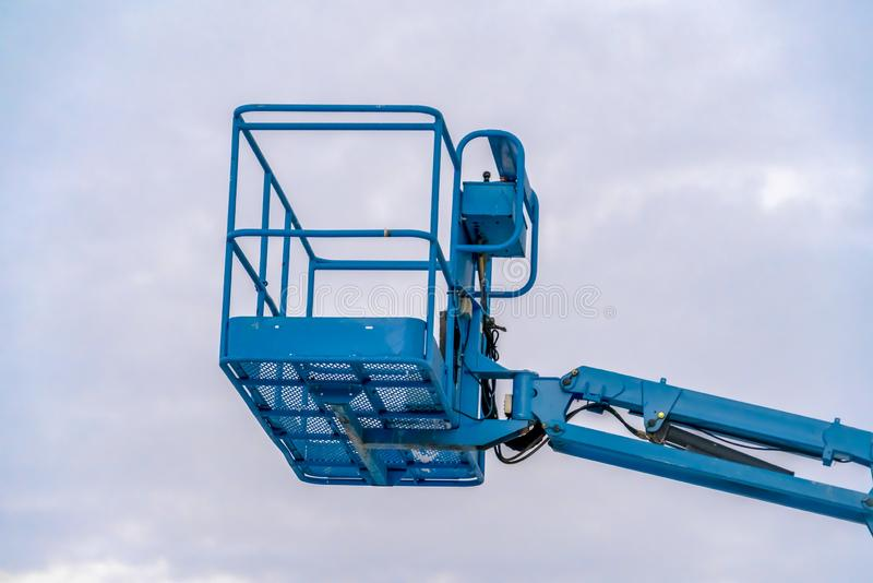 Empty boom lift and cloudy sky in Eagle Mountain. A blue empty boom lift against cloudy sky in Eagle Mountain, Utah. It is a mechanical device used by workers stock image