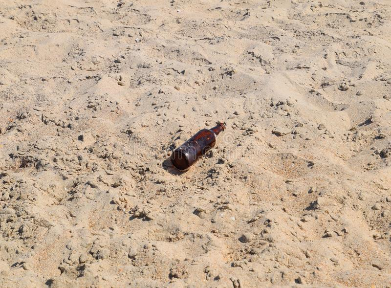 An empty bottle of beer is lying on the sand stock photography