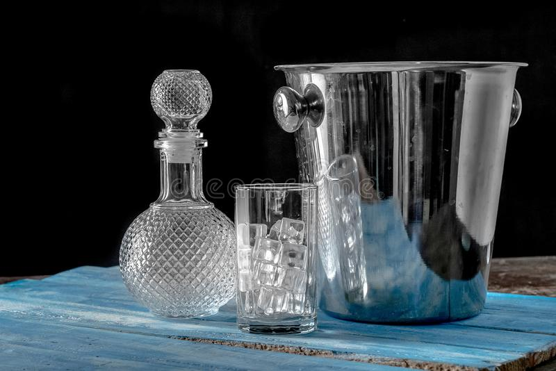 Empty bottle and Glass of Ice cube on blue wooden table background. royalty free stock images