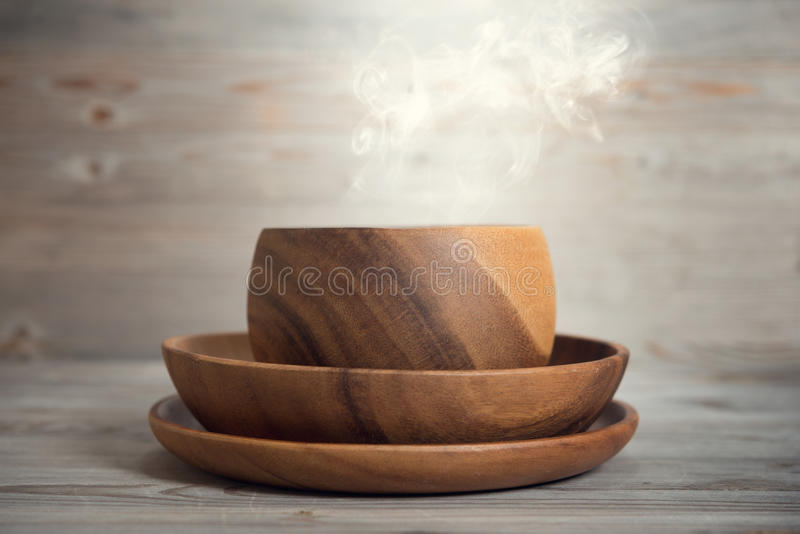 Empty bowl with hot smoke. On old wooden table. Dramatic light royalty free stock photo