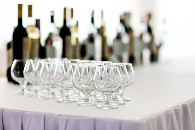 Empty brandy glasses in a row and bottles of alcohol in a backdrop royalty free stock image